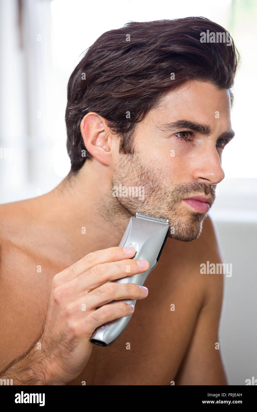 Man shaving with trimmer - Stock Image