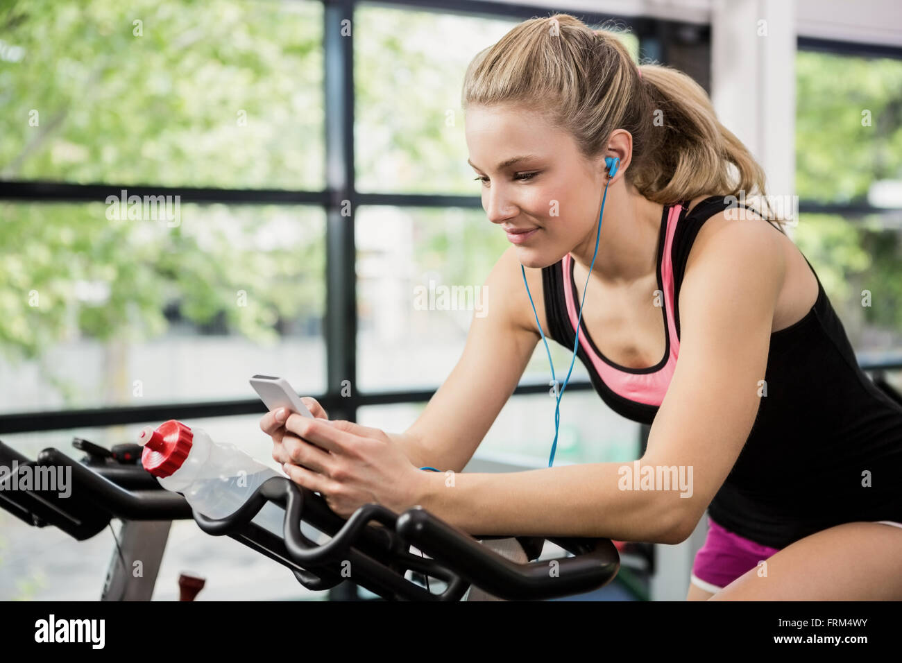 Woman listening music and text messaging - Stock Image