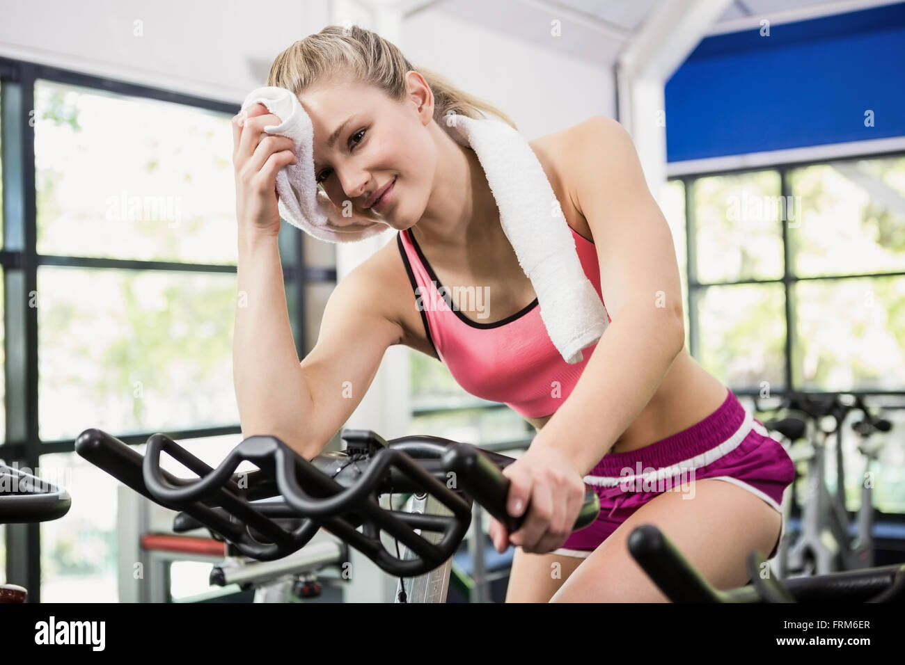 Tired woman wiping his face after workout - Stock Image