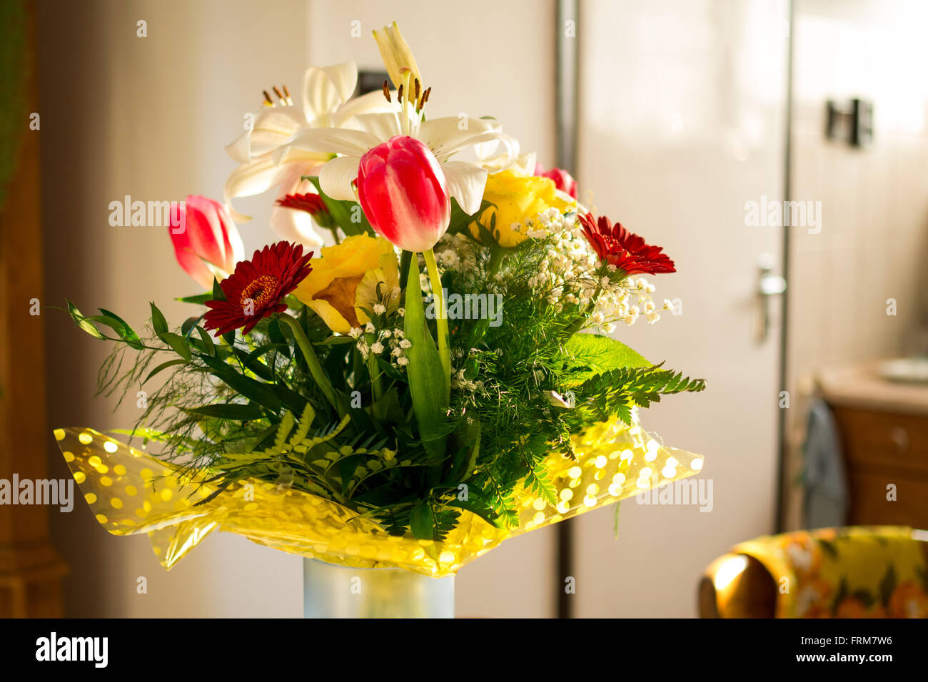 Flower bouquet with vase against blurry background. - Stock Image