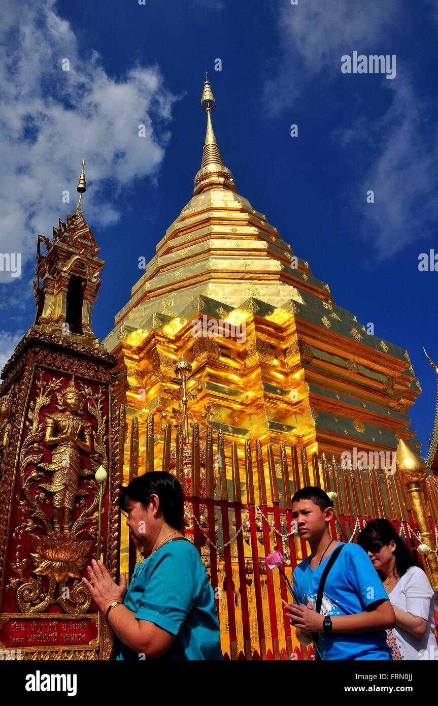 Chiang Mai. Thailand:   Devout Thais, hands clasped in prayer, encircle the sacred golden Chedi at Wat Doi Suthep - Stock Image
