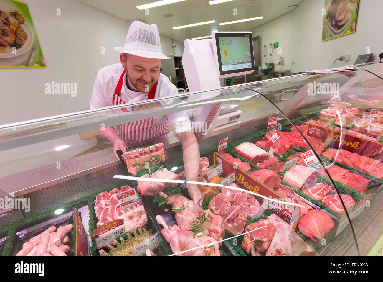 A butcher at a Morrisons fresh look store - Stock Image