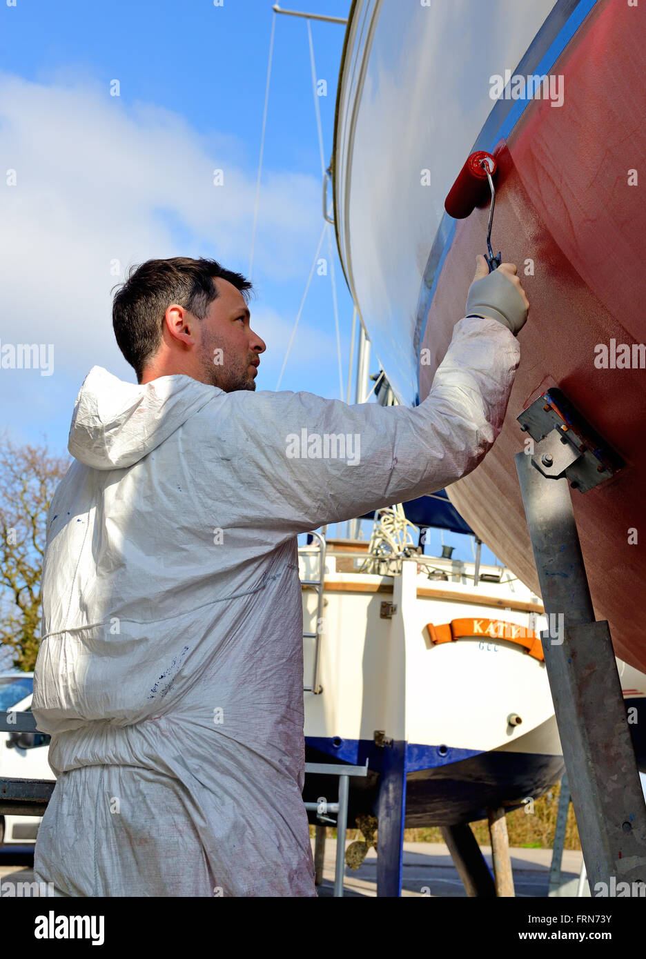 Marina yard worker painting antifouling paint (marine weed preventative )by roller on a keeled yacht for the new - Stock Image