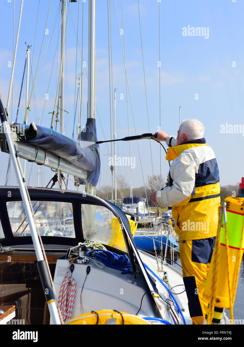 Boat owner using a water jet spray to clean the and sail cover and  top sides on his yacht in the marina - Stock Image
