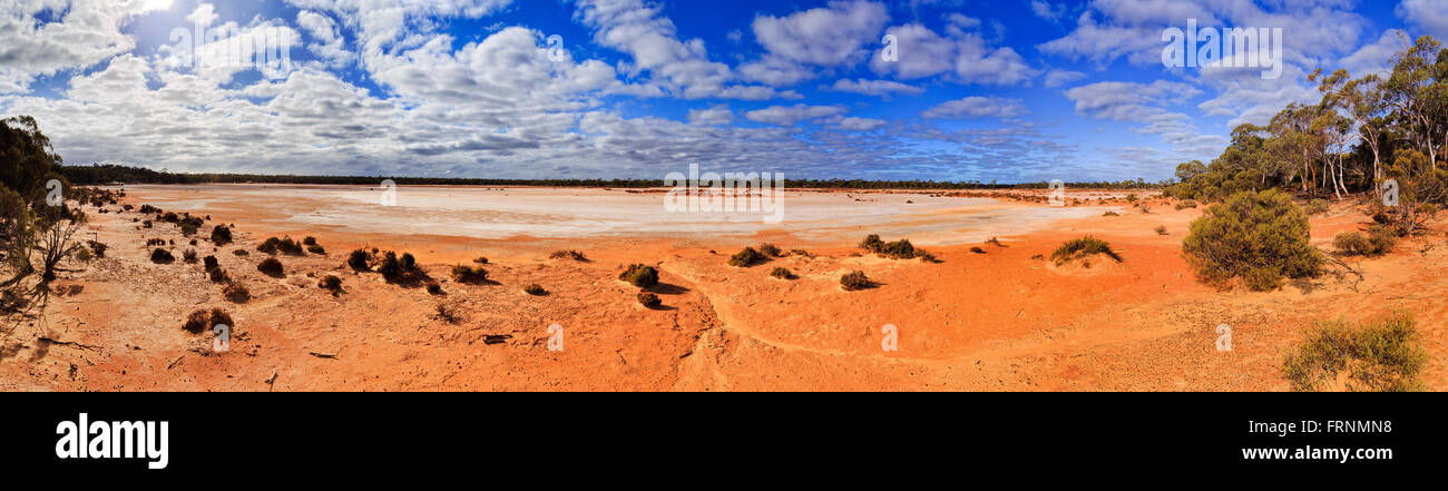 wide open plain view of dry solt covered red soil evaporated lake in Western Australia. Arid outback surrounded - Stock Image