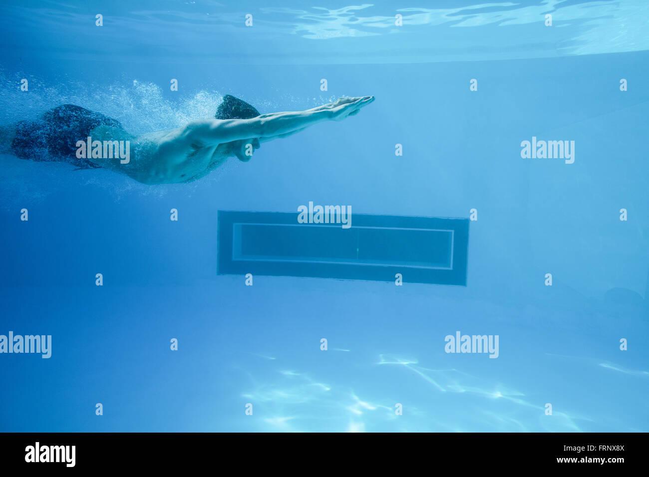 Man swimming underwater at resort - Stock Image