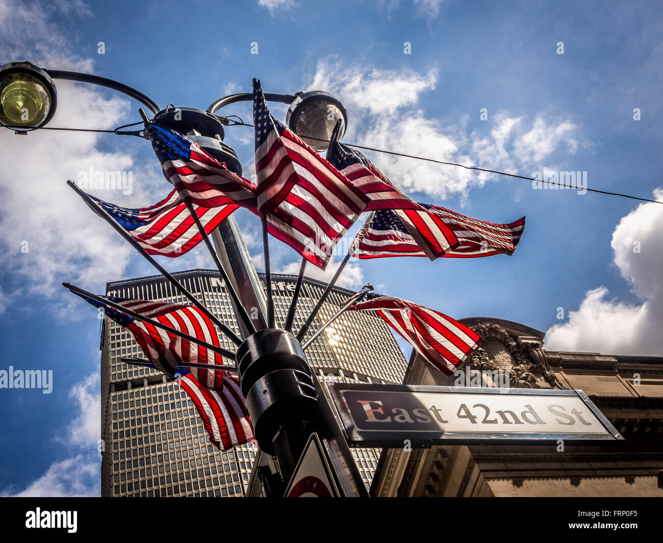 East 42nd St sign and group of American flags on lamppost, New York City, USA. - Stock Image