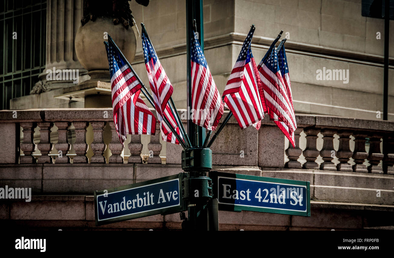 East 42nd St sign and group of American flags on lampost, New York City, USA. Stock Photo