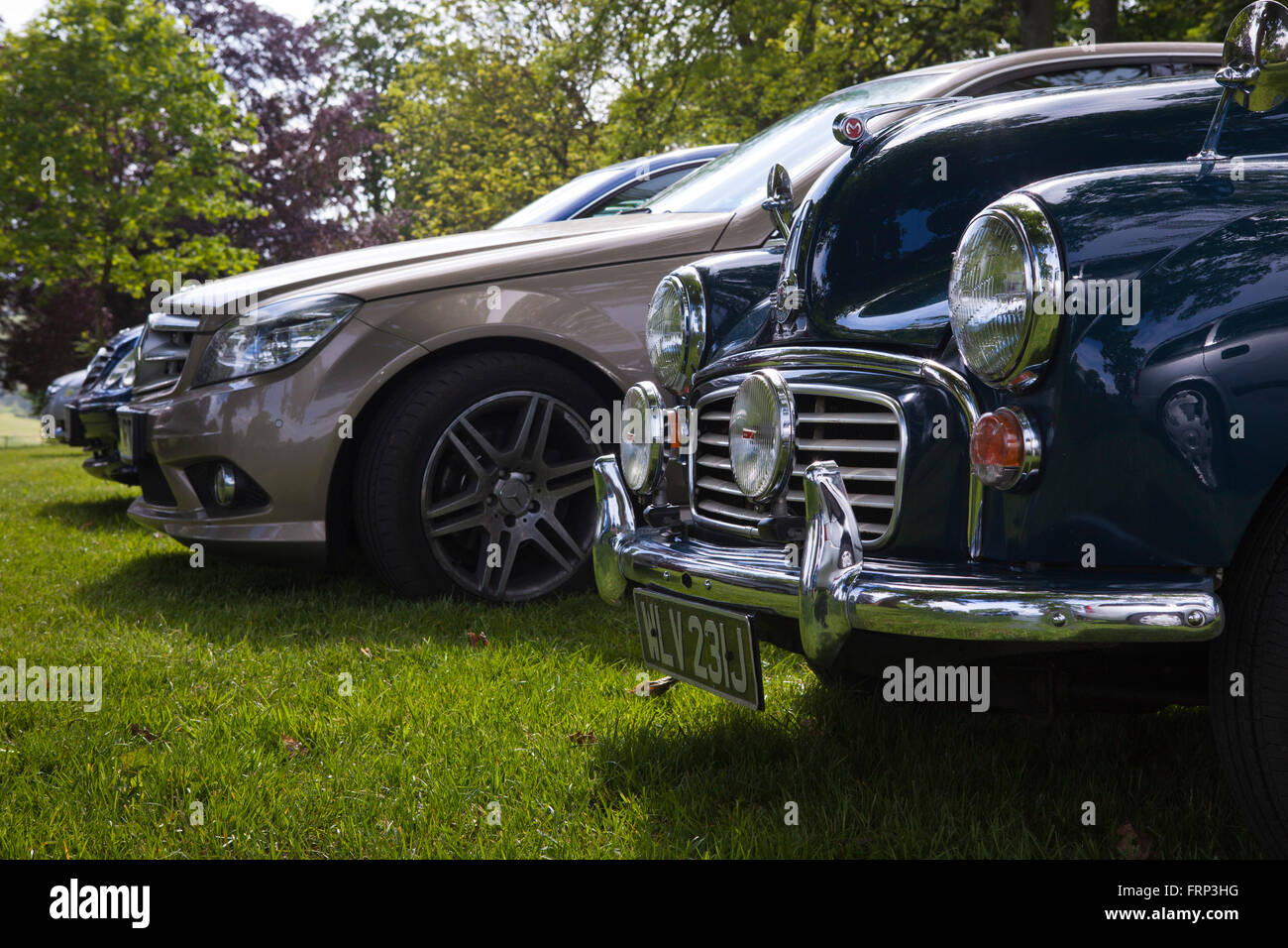 An old morris minor motor car parked amongst new cars ina grass car ...