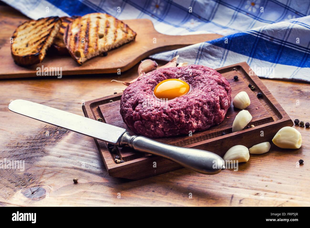 Raw beef .Tasty Steak tartare. Classic steak tartare on wooden board. Ingredients: Raw beef meat salt pepper egg - Stock Image