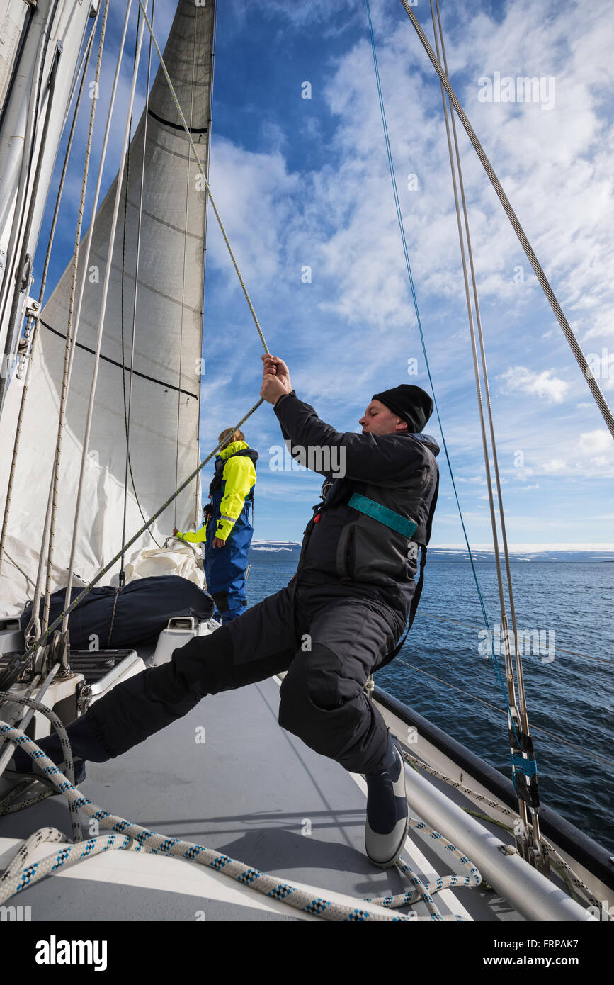 Manually hoisting the headsail while sailing in Westfjords of Iceland - Stock Image