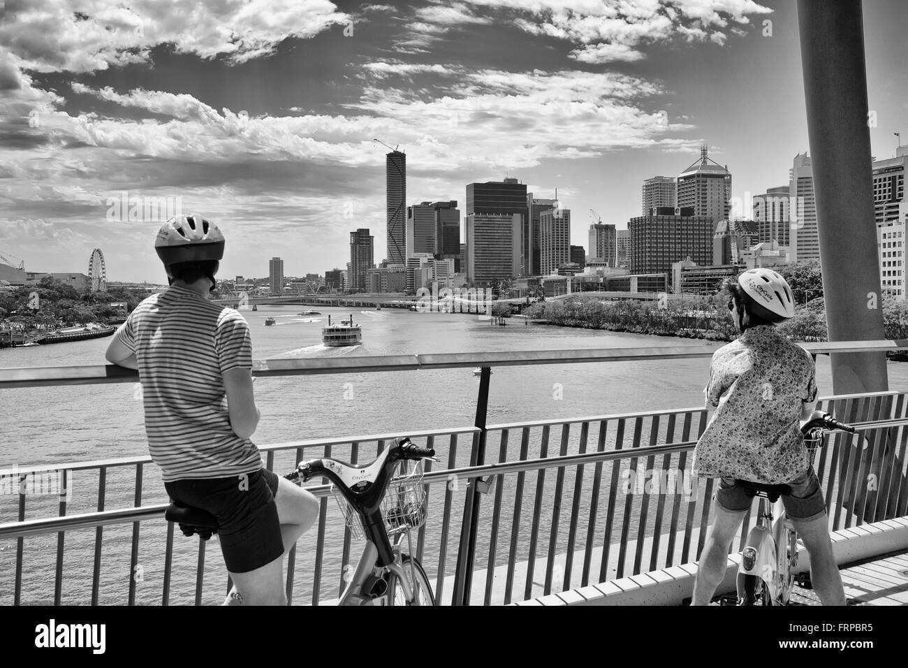 cyclists stop to admire the view of the city beyond the brisbane river on the Goodwill bridge - Stock Image