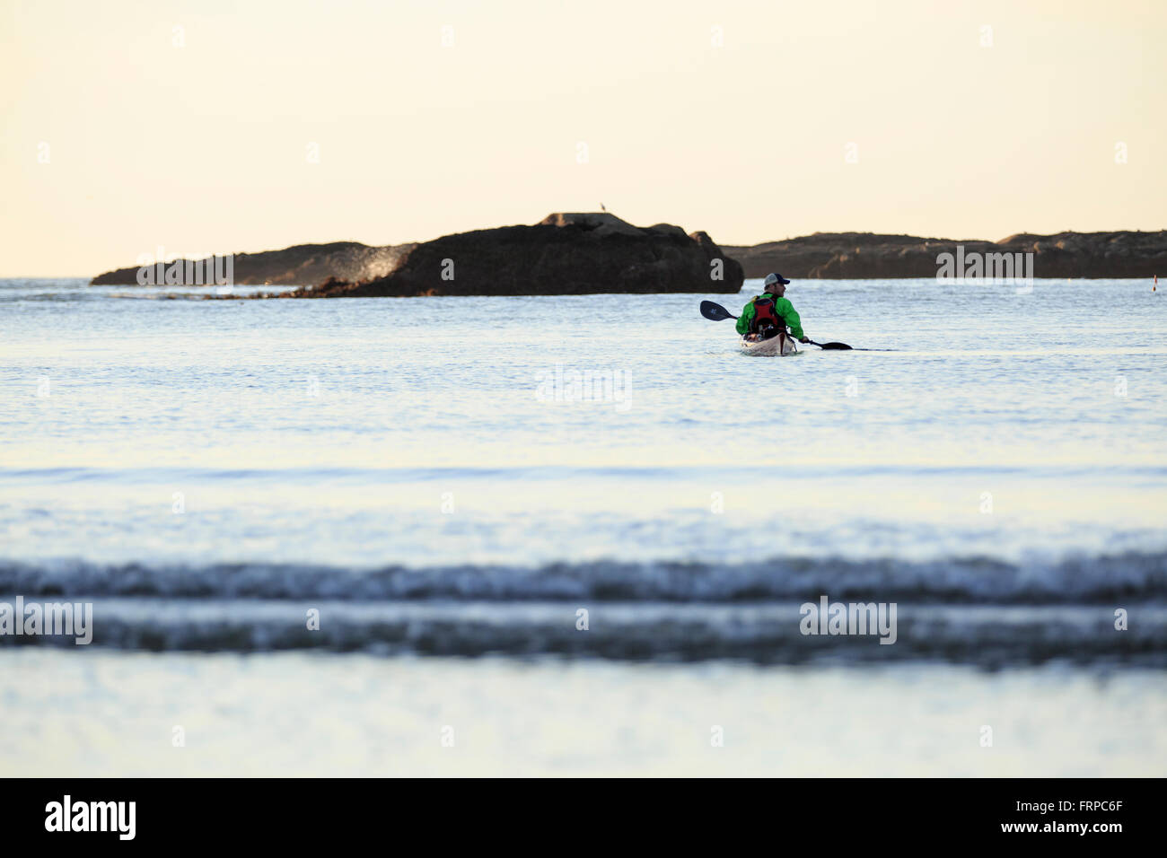 Kayaker paddles just off of the Oregon coast. - Stock Image