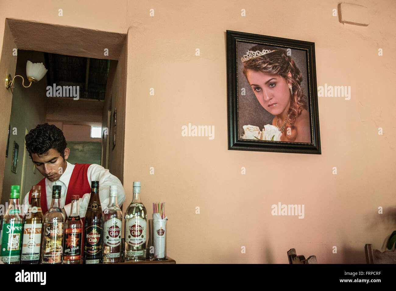 A young Cuban bartender prepares drinks at Restaurante Mimi. Trinidad, Cuba - Stock Image