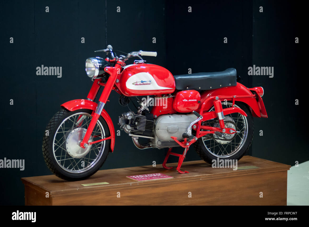 Single old fashioned red and white Harley Davidson- Aermacchi motorcycle on wooden display stand in front of black - Stock Image