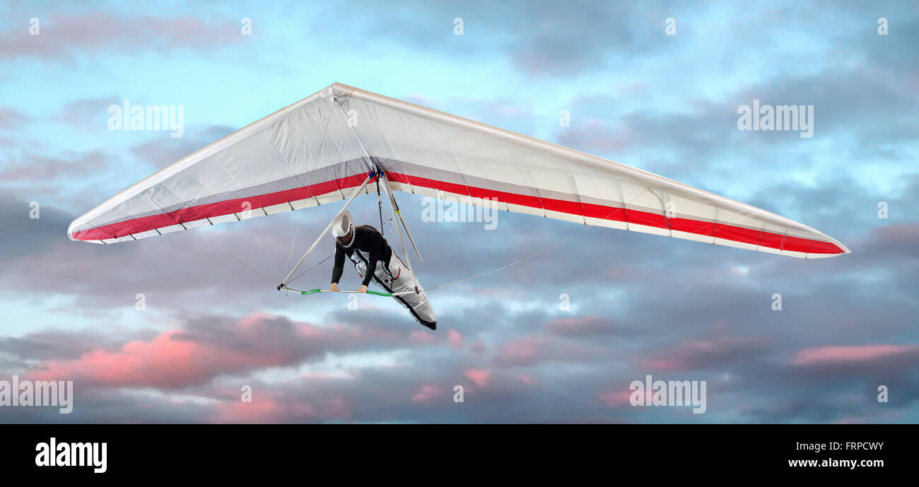 Man in a harness hang-gliding at sunset against pretty pink clouds in the sky in a close up view - Stock Image