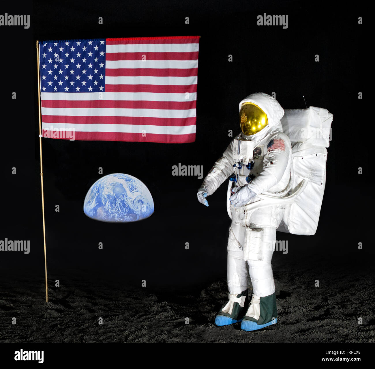 Model of single American NASA astronaut for display about lunar exploration with posted flag far from earth - Stock Image
