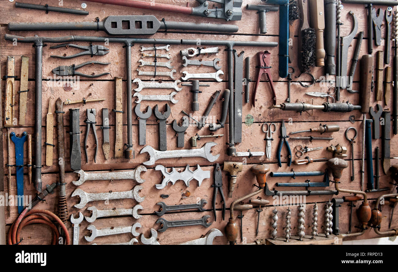 Display of various iron wrenches, drill bits, clamps and other tools on old wooden wall - Stock Image