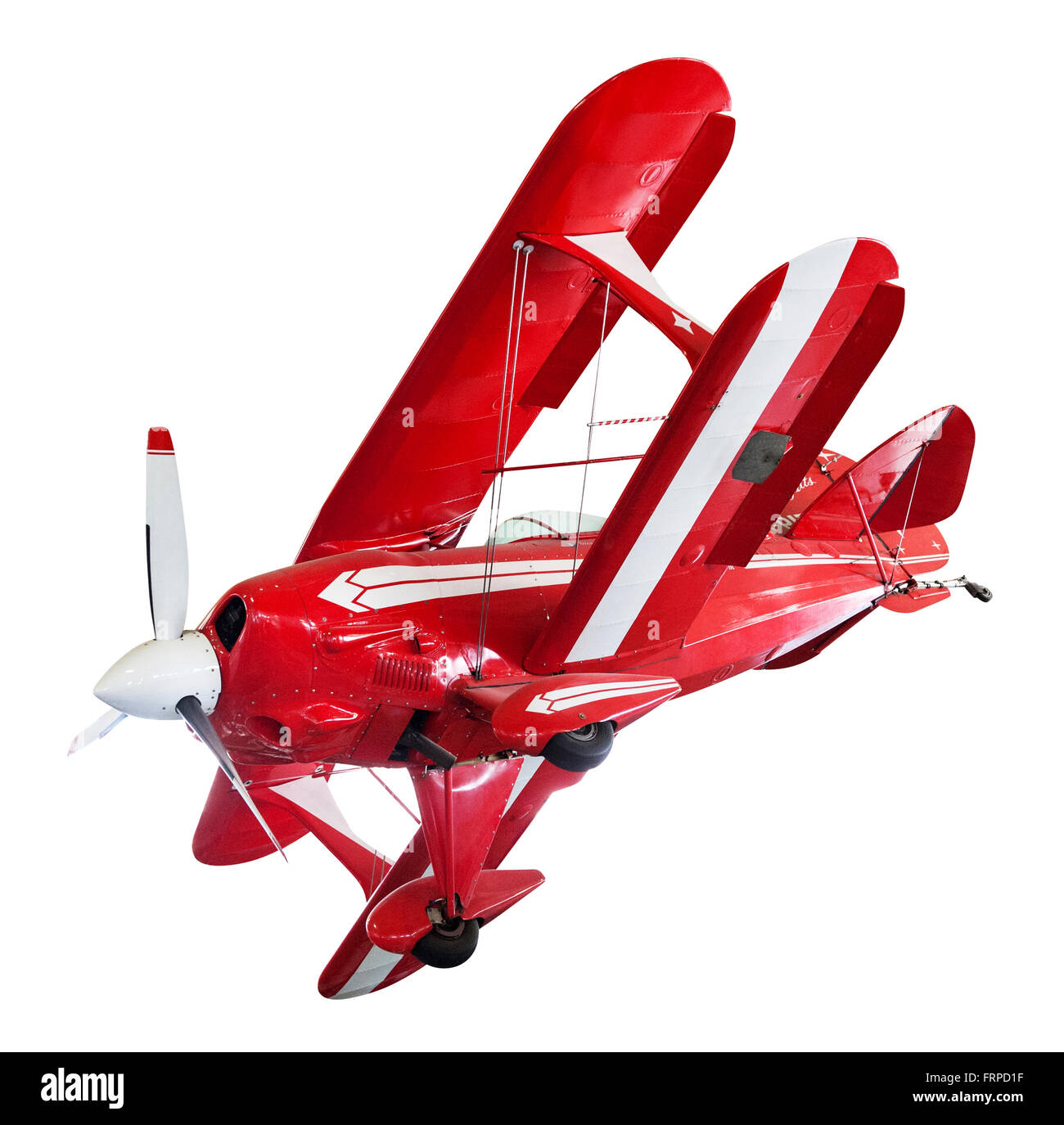 Vintage red and white bi-plane isolated on white positioned as though banking in flight - Stock Image