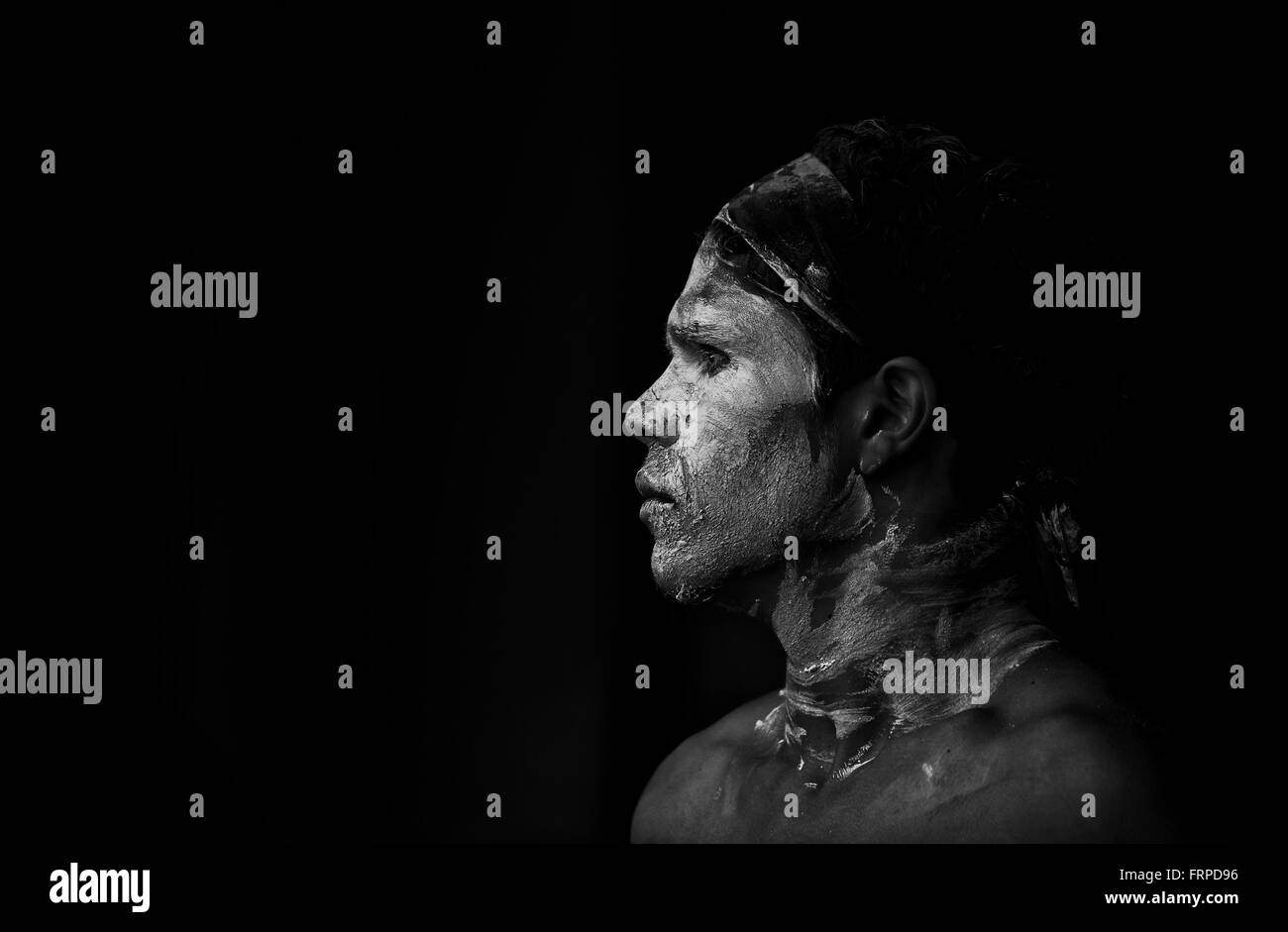 Aboriginal Australian dancer with face paint standing in shadow. Atmospheric black&white profile portrait . - Stock Image