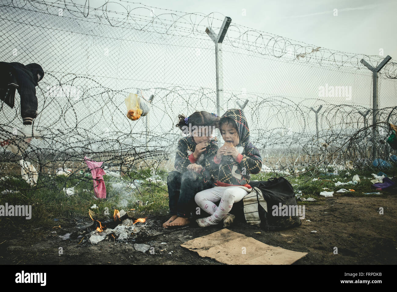 Idomeni refugee camp on the Greece Macedonia border, two little girls warm themselves at a campfire, Idomeni, Central - Stock Image