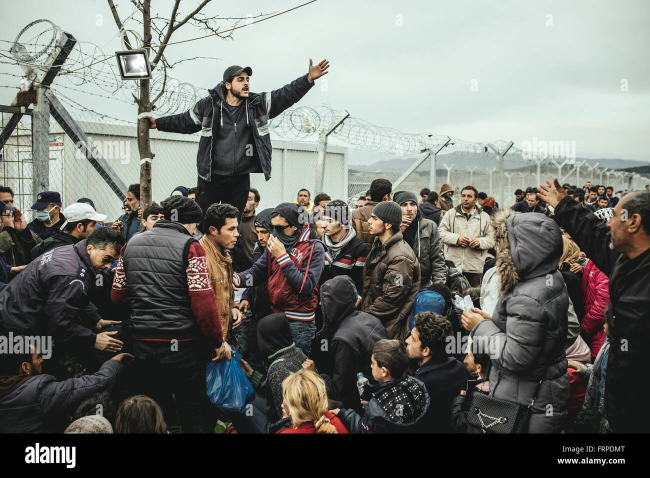 Idomeni refugee camp on the Greece Macedonia border, refugees waiting at a checkpoint, a man translates the official - Stock Image