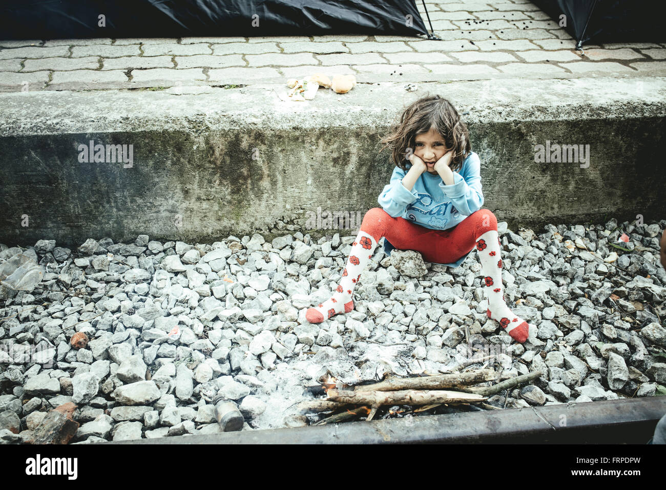 Idomeni refugee camp on Greek Macedonia border, a child sits on the platform at the station, Idomeni, Central Macedonia, - Stock Image
