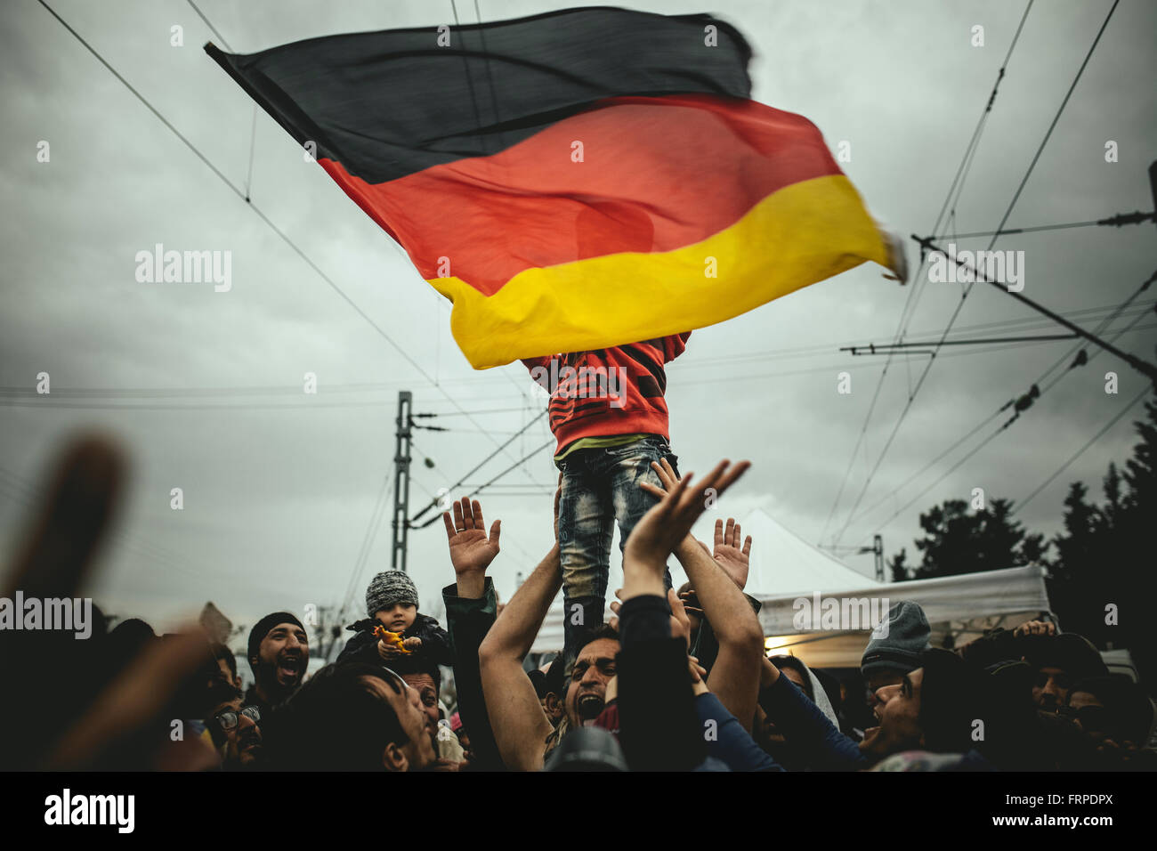 Idomeni refugee camp on Greek Macedonia border, Syrian refugees protest, Pro-Merkel rally, a child waves a german - Stock Image