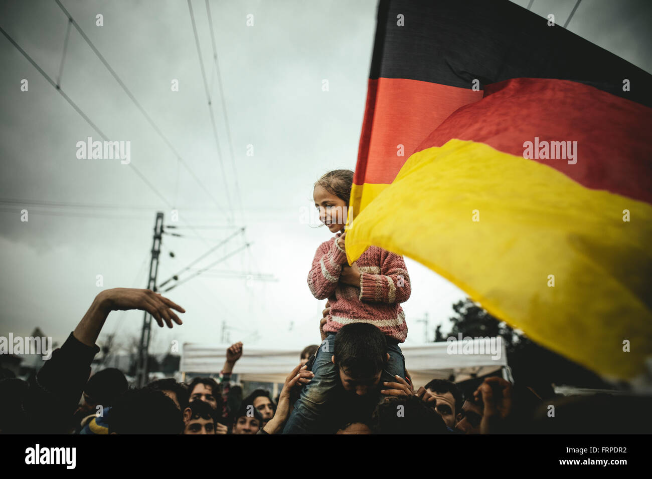 Idomeni refugee camp on Greek Macedonia border, Syrian refugees protest, Pro-Merkel rally, a girl waves a german - Stock Image