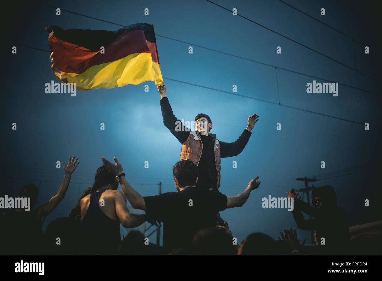 Idomeni refugee camp on Greek Macedonia border, Syrian refugees protest, Pro-Merkel rally, boy waves a german flag, - Stock Image