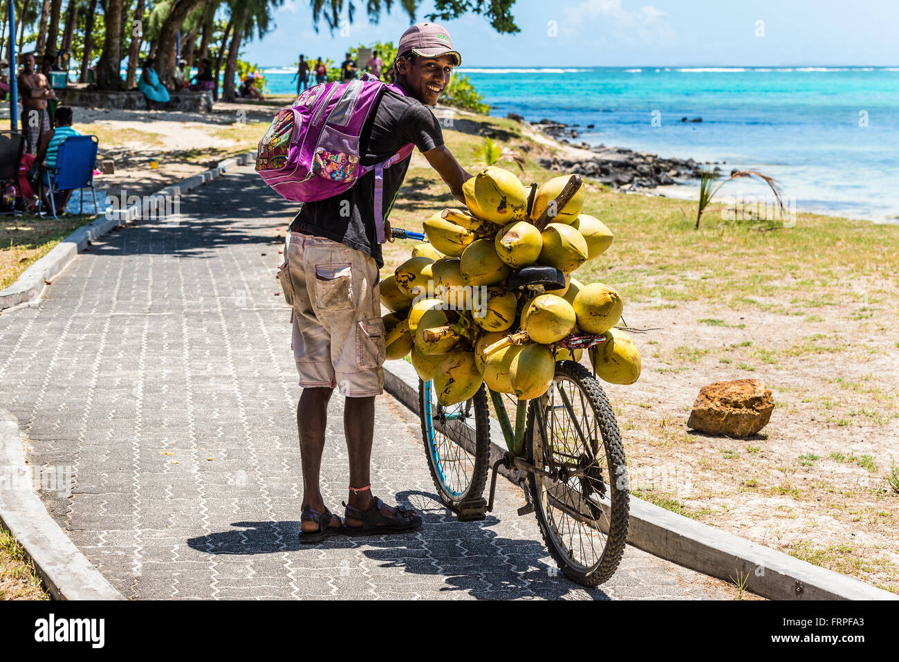 Mauritius young man selling coconuts from his bike on the beach Blue Bay, Mauritius. - Stock Image