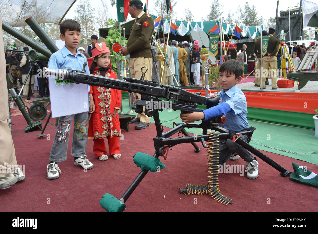Quetta, Pakistan. 23rd Mar, 2016. A Pakistani boy poses for photos with a machine gun during a military exhibition - Stock Image
