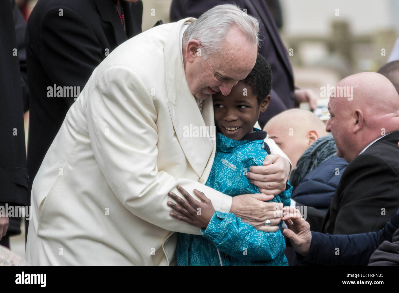 Vatican City, Vatican. 23rd Mar, 2016. Pope Francis hugs a boyduring his Weekly General Audience in St. Peter's - Stock Image