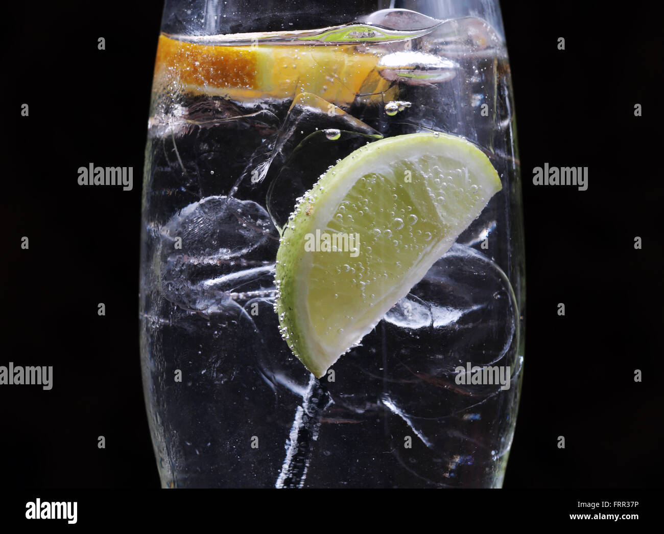 Gin and tonic with ice, lemon and lime. - Stock Image