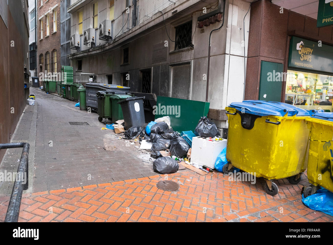 Rubbish bins and litter in a side street in Birmingham city centre, West Midlands, England, UK - Stock Image
