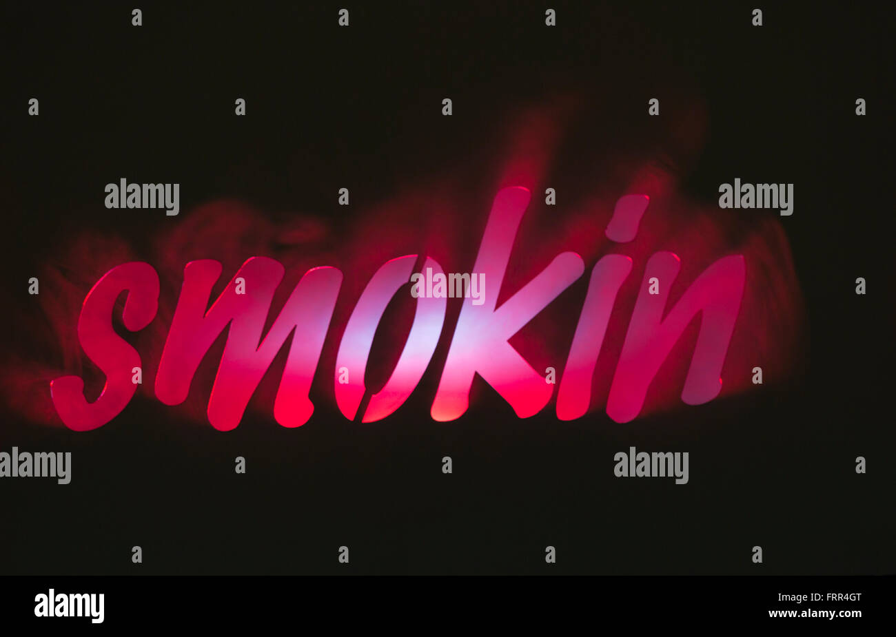 Lit smokin sign with smoke set on black background Stock Photo