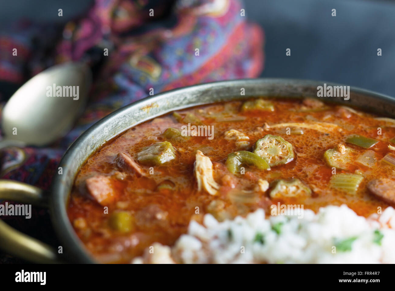 Copper pot filled with sausage gumbo and a scoop of rice. - Stock Image