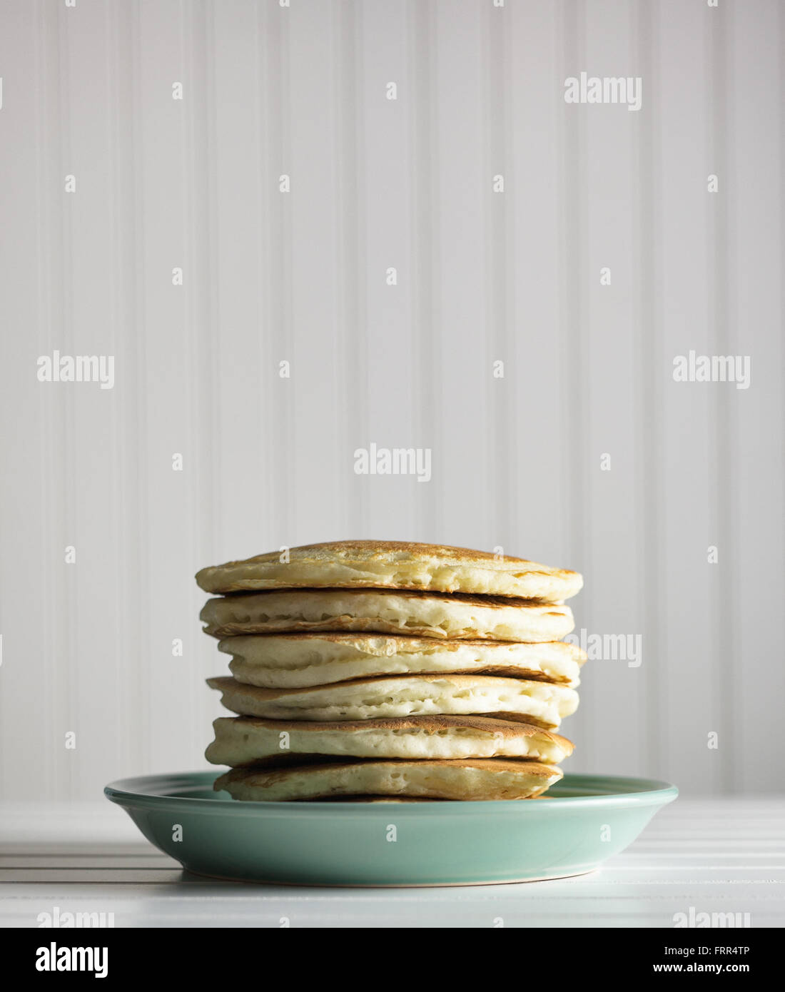 Tall stack of pancakes on a blue plate against a white background. - Stock Image