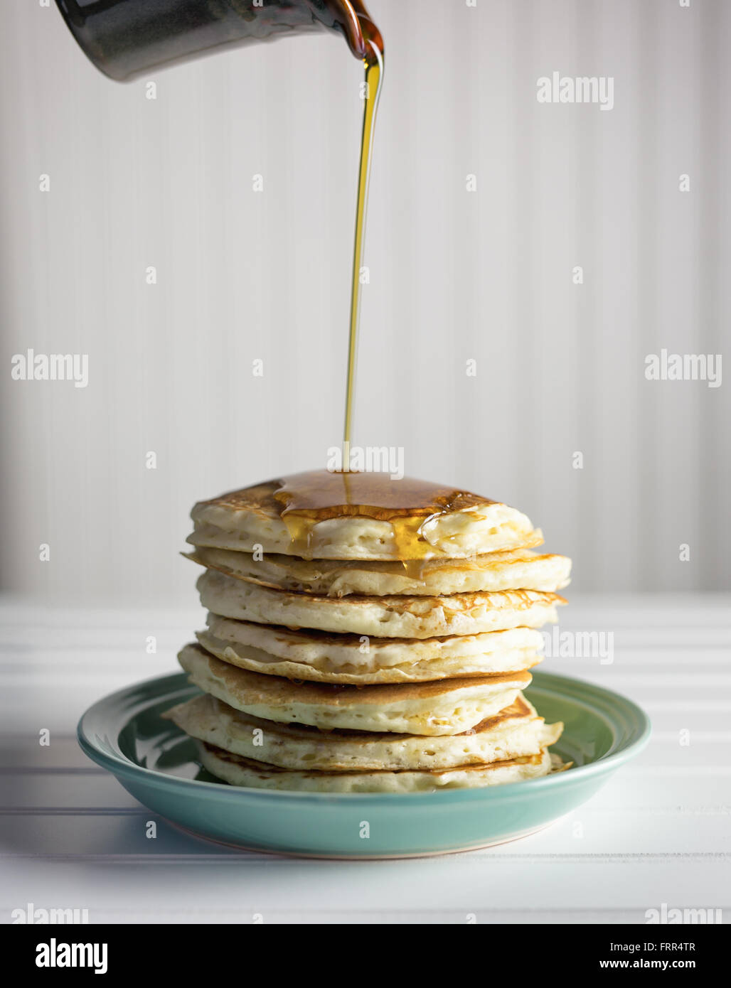 Maples syrup being poured over a tall stack of pancakes. - Stock Image