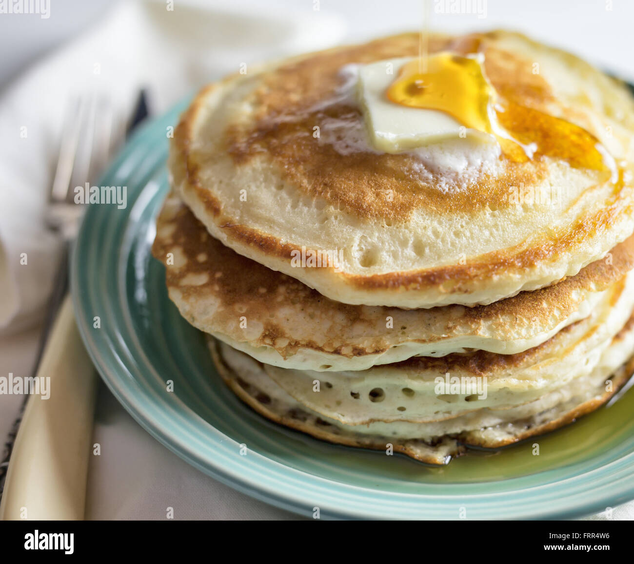 Stack of pancakes with butter and maple syrup. - Stock Image