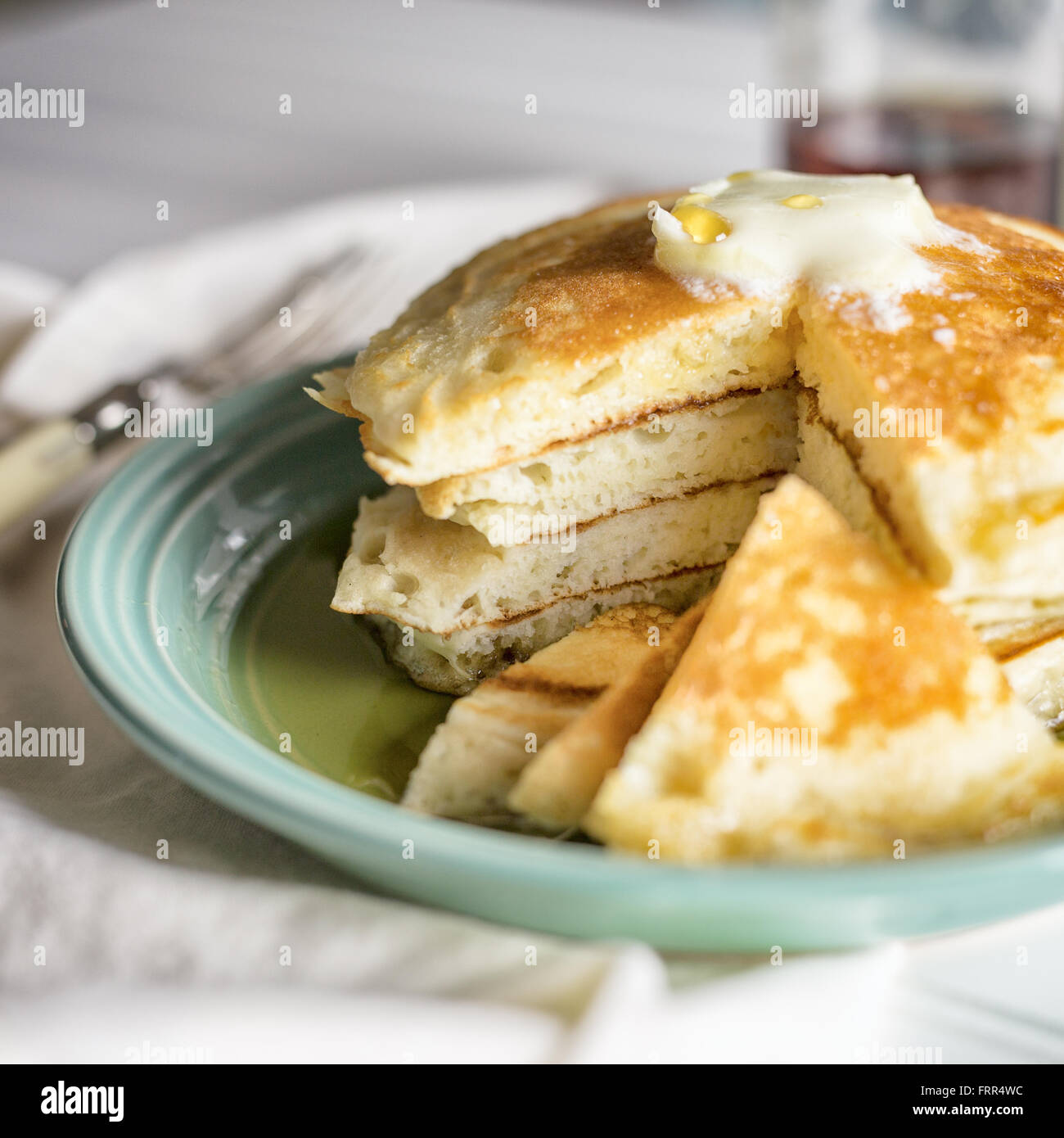 A small stack of sliced pancakes with butter and syrup. Stock Photo