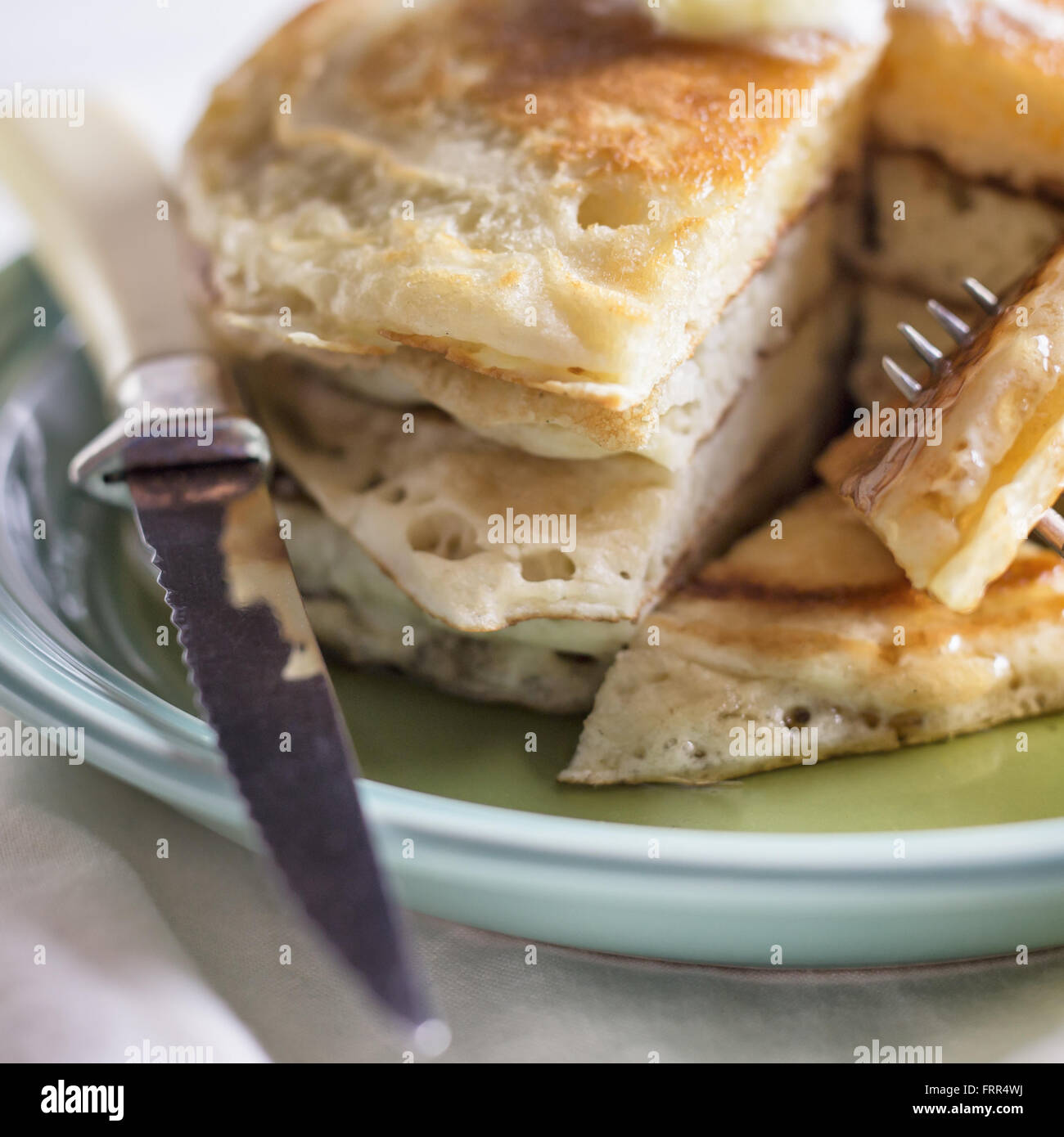 A small stack of sliced pancakes with butter and syrup. - Stock Image