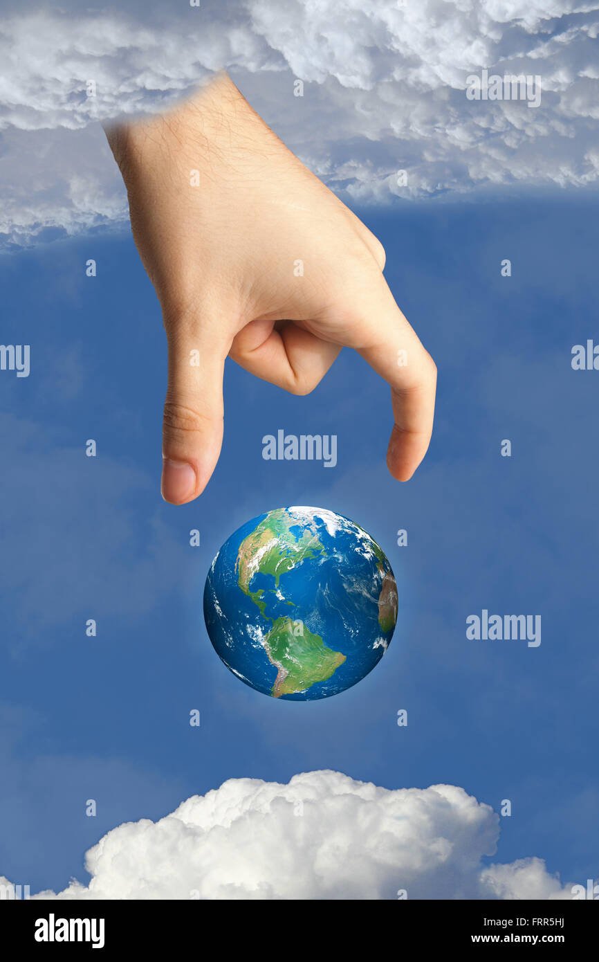 god's hand putting earth in heaven in the sky between the clouds, symbolizing faith and religion. images used - Stock Image