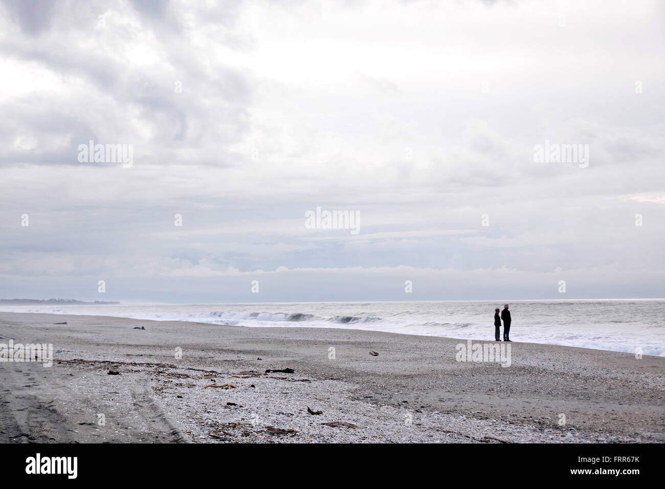 Couple at lonely beach, Westland National Park,  South island,  New Zealand - Stock Image