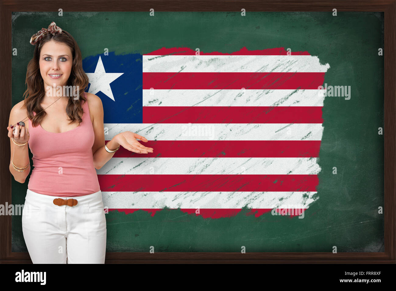 Beautiful and smiling woman showing flag of Liberia on blackboard, presentation for tourism and marketing research - Stock Image