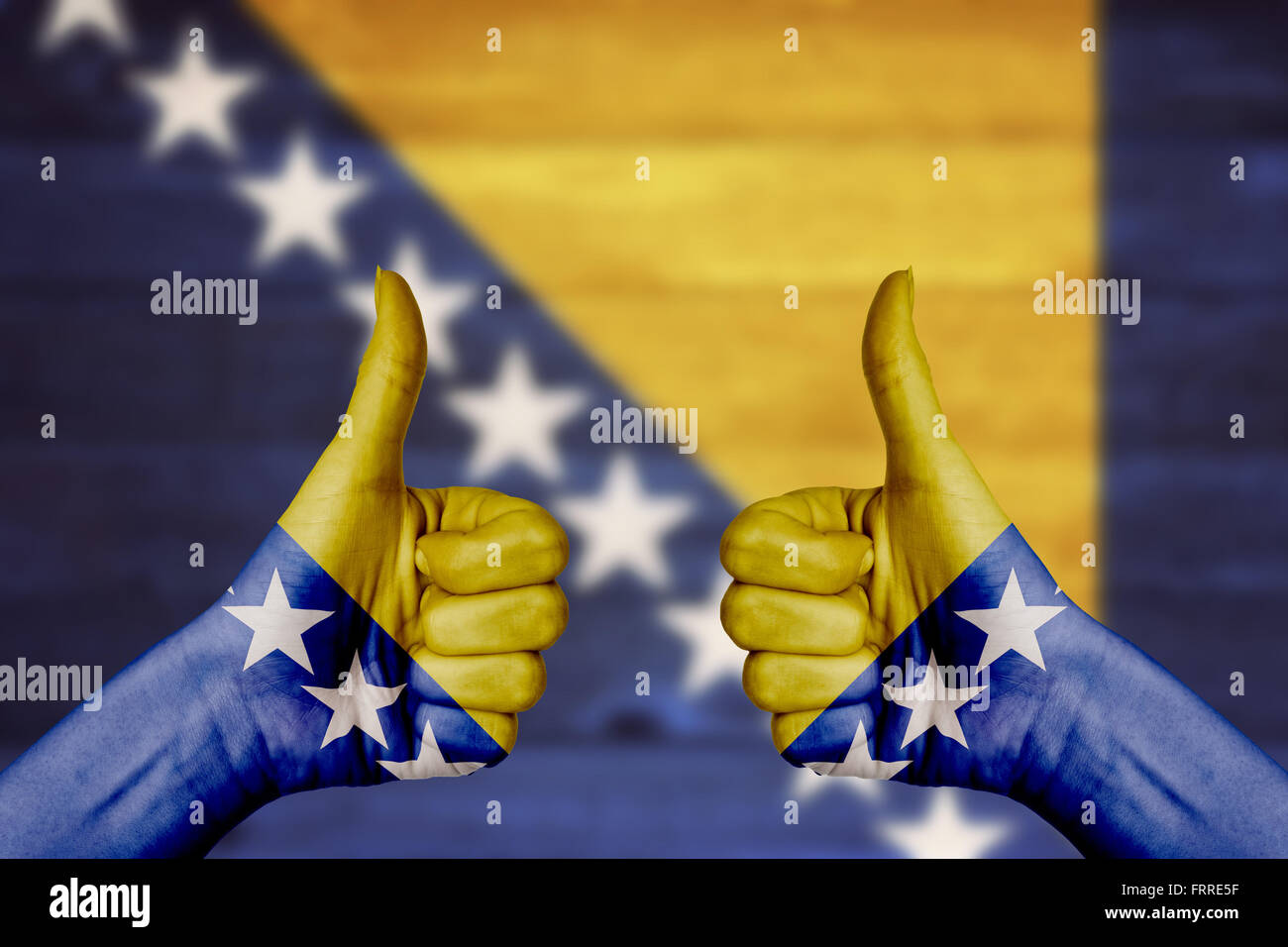 Bosnia and Herzegovina flag painted on female hands thumbs up with blurry wooden background - Stock Image