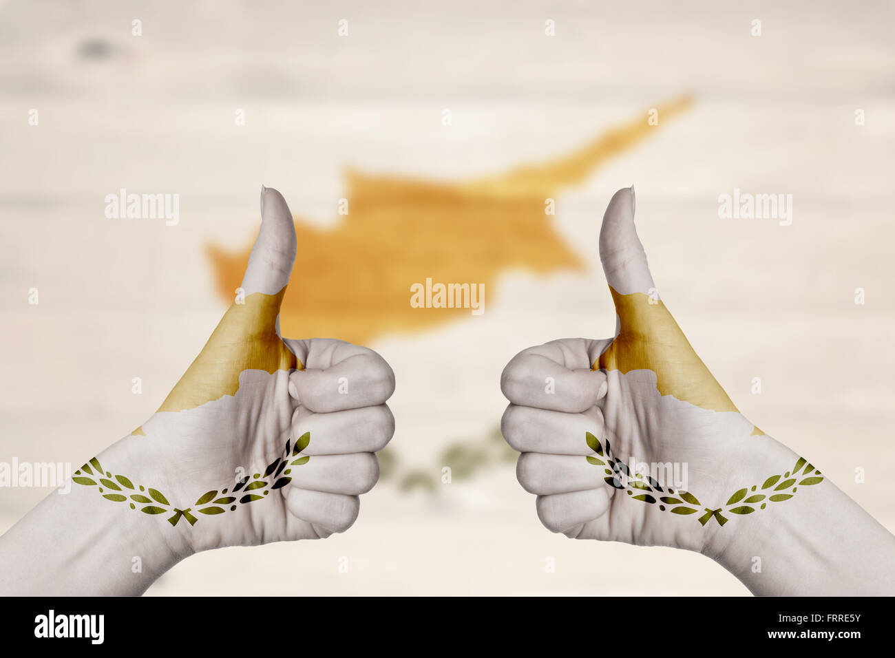 Cyprus flag painted on female hands thumbs up with blurry wooden background - Stock Image