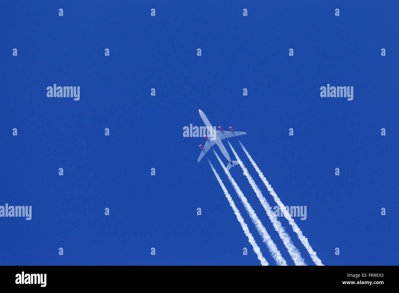 Engine exhaust contrails - cirrus aviaticus - forming behind four-engine Airbus A340 plane against blue sky - Stock Image