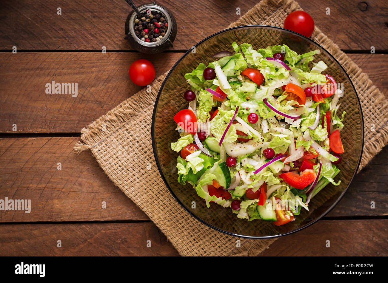 Dietary salad with fresh vegetables (tomato, cucumber, Chinese cabbage, red onion and cranberries). Top view - Stock Image