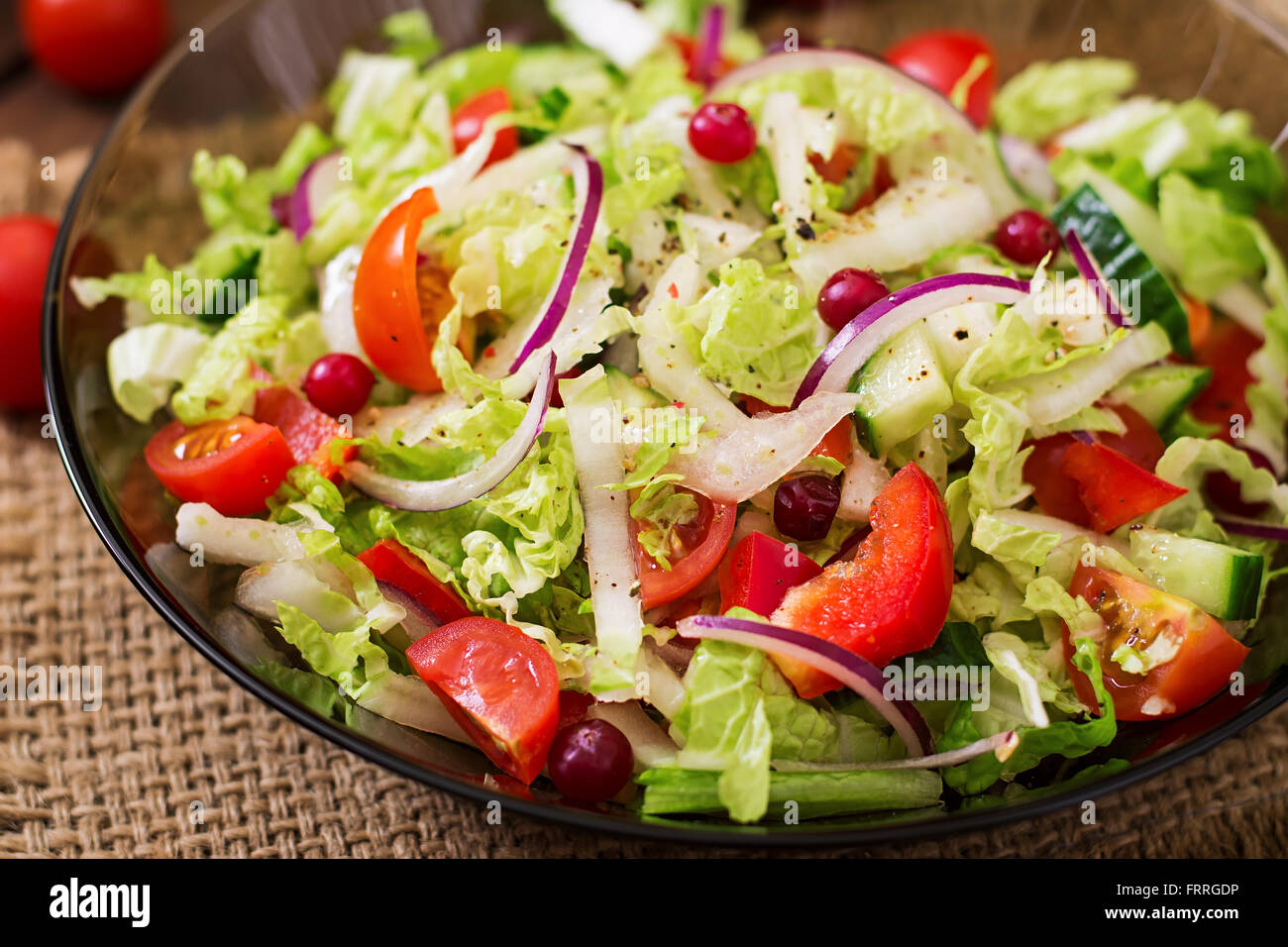 Dietary salad with fresh vegetables (tomato, cucumber, Chinese cabbage, red onion and cranberries) - Stock Image